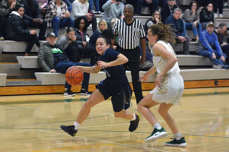 Liberty's Taylin Smith drives around a Jesuit defender during the Falcons' game against the Crusaders Saturday, March 2, at Jesuit High School.