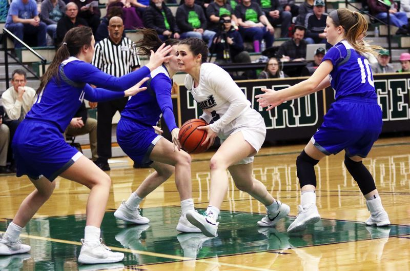 PMG PHOTO: DAN BROOD - Tigard High School junior Kennedy Brown is surrounded by Grants Pass defenders in the first half of Saturday's second-round state playoff game.