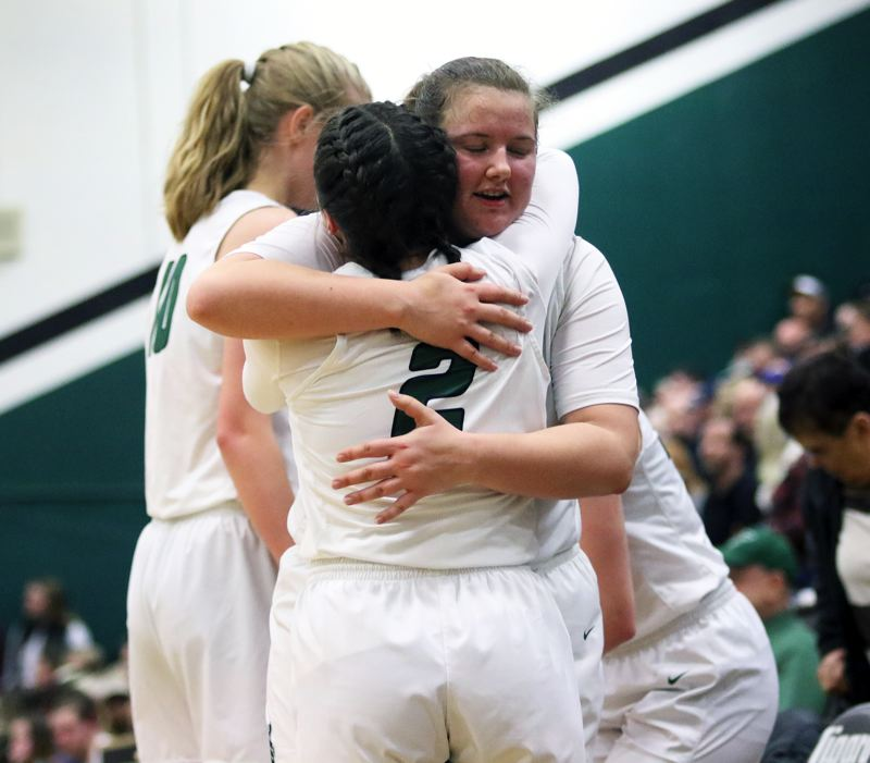 PMG PHOTO: DAN BROOD - Tigard High School junior Kennedy Brown (2) hugs senior Dani Lyons near the end of Saturday's Class 6A state playoff game.