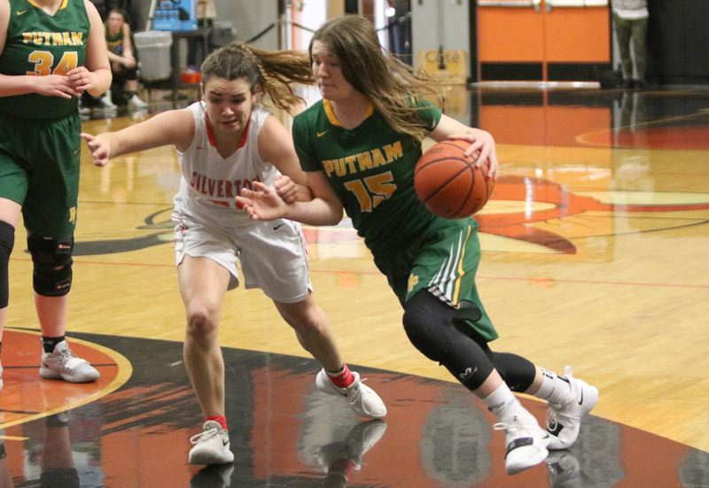 PMG PHOTO: JIM BESEDA - Putnam's Maddy Olma (15) drives on Silverton's Josslyn Ames during the first half of Saturday's first round of the OSAA Class 5A girls' basketball playoffs. Silverton downed the Kingsmen 57-36.