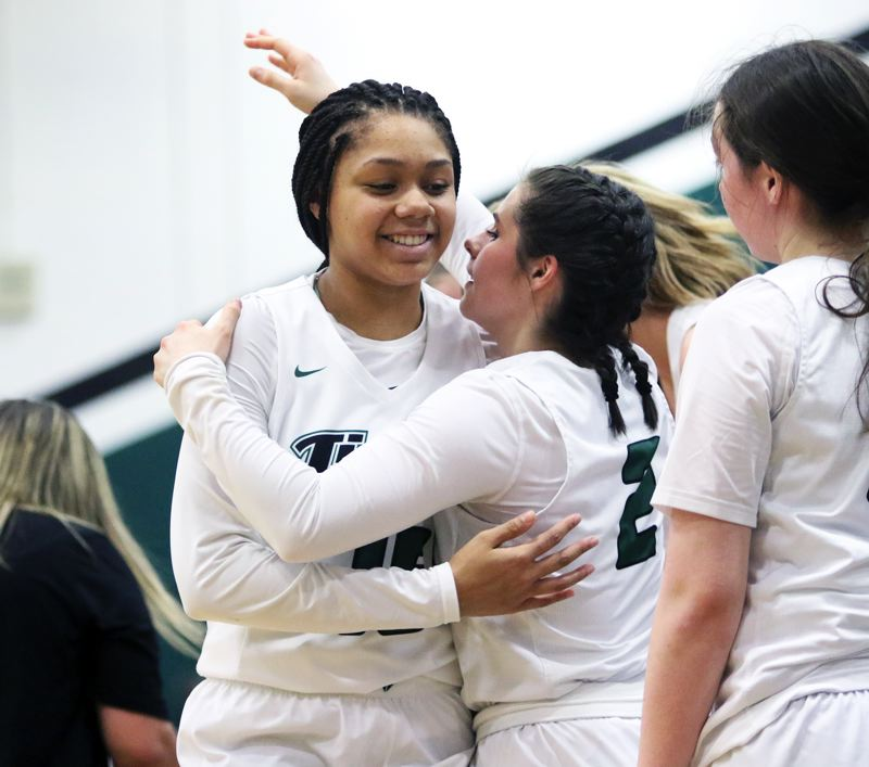 PMG PHOTO: DAN BROOD - Tigard sophomore Ajae Holdman (left) hugs junior Kennedy Brown during the final moments of the Tigers' state playoff win over Grants Pass on Saturday.