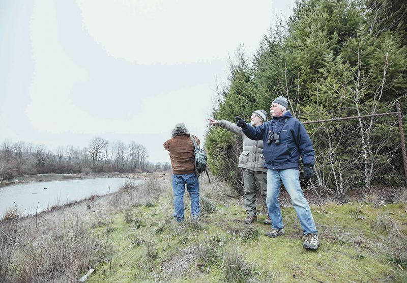 PORTLAND TRIBUNE: JONATHAN HOUSE - Environmentalists fear that developer Jordan Schnitzer will demolish the former Wapato jail building and chop down a three-acre swath of trees that buffer the site from nearby Smith and Bybee lakes. From left, Bob Sallinger, Dale Svart and Troy Clark check out Bybee Lake that sits just on the other side of the Wapato property.