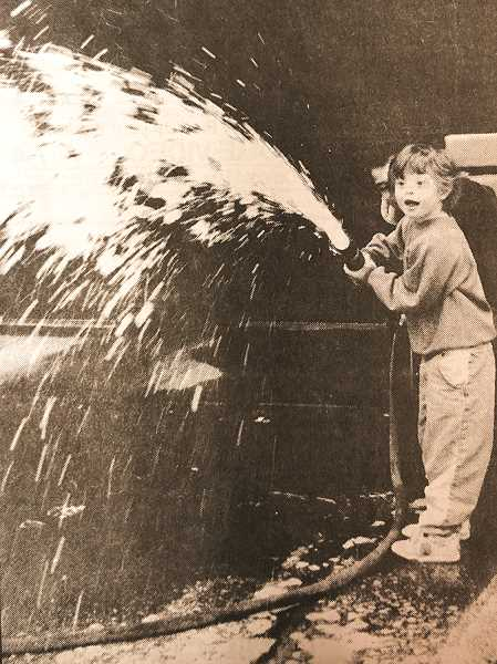 CENTRAL OREGONIAN FILE PHOTO  - March 3, 1994: Alexis Gray, a student at Ochoco Elementary Independent Life Skills, sprays fire-retardant foam from a fire hose during a tour at the fire station Friday.