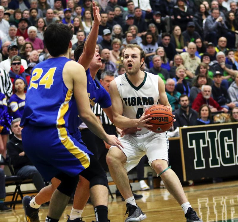 PMG PHOTO: DAN BROOD - Tigard High School senior Stevie Schlabach (right) looks to get to the basket during the first quarter of the Tigers' state playoff win over Barlow.