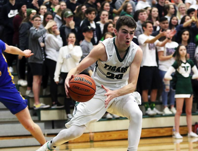 PMG PHOTO: DAN BROOD - Tigard High School senior Luke Ness looks to make a move on the baseline during the Tigers' state playoff win over Barlow.