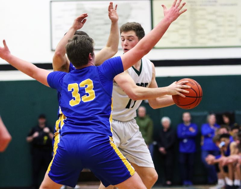 PMG PHOTO: DAN BROOD - Tigard High School senior Eric Sawin (right) is trapped by a pair of Barlow players, including junior Jaren Hunter (33) during Saturday's state playoff game.