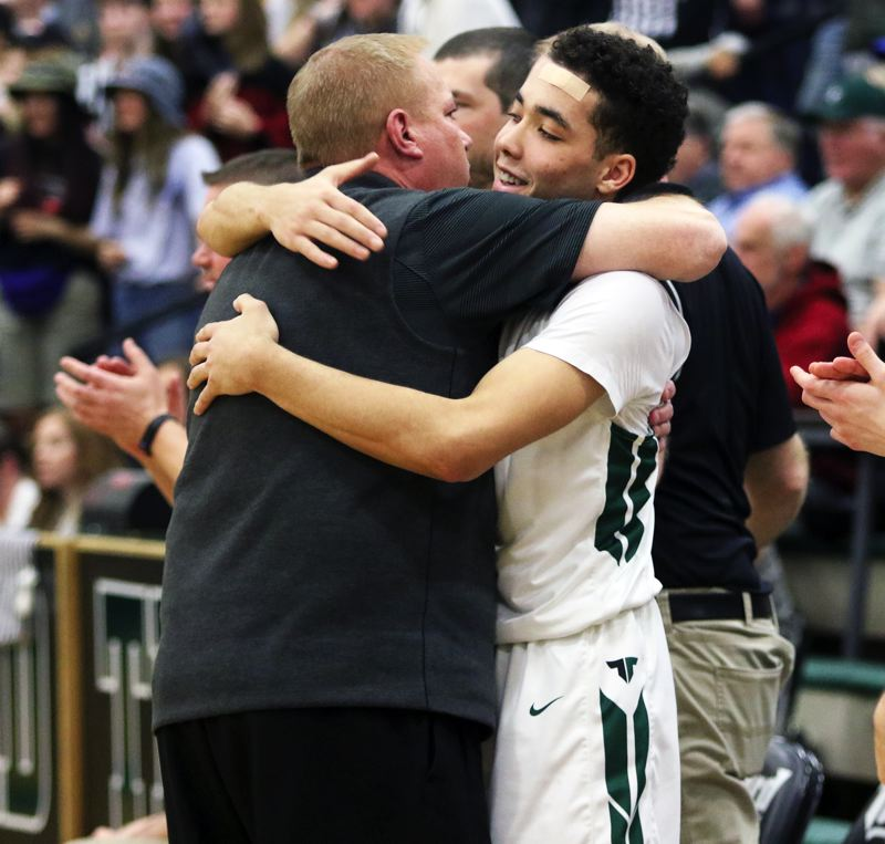 PMG PHOTO: DAN BROOD - Tigard High School sophomore Drew Carter gets a hug from Tiger head coach Shawn Alderman during the final moments of the Tigers' state playoff win over Barlow on Saturday.