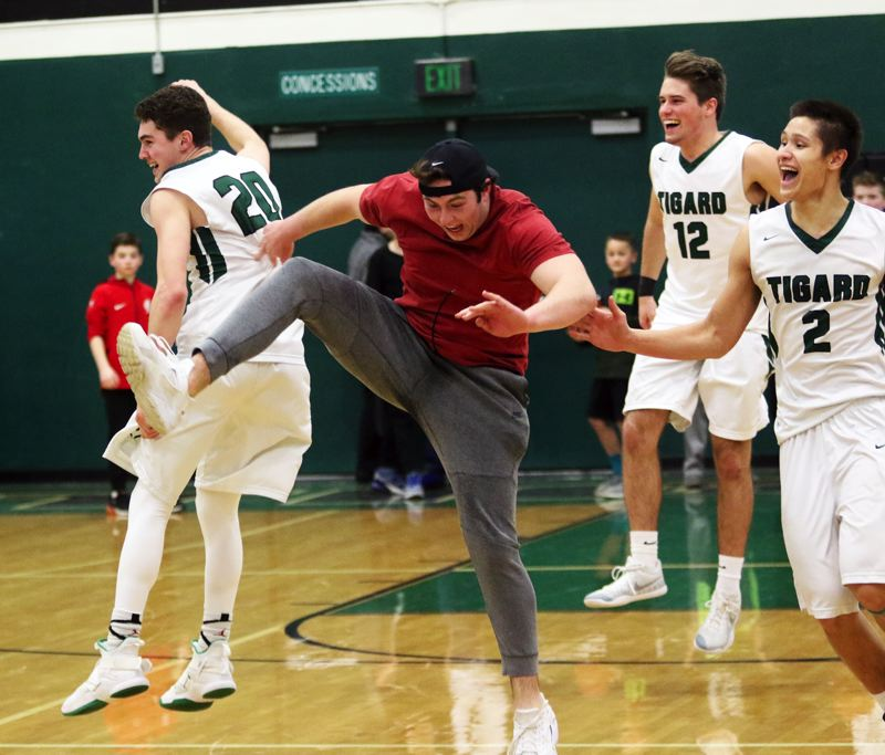 PMG PHOTO: DAN BROOD - Tigard players Luke Ness (20), Carson Crist (12) and Jazz Ross (2), as well as Tigard High School senior Hayden McDonald, celebrate following the Tigers' 85-74 state playoff win over Barlow on Saturday.