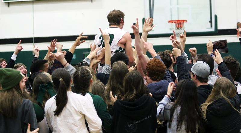 PMG PHOTO: DAN BROOD - Tigard High School senior Peyton Sievke is lifted up by Tigard players and students following the Tigers' state playoff win over Barlow on Saturday.