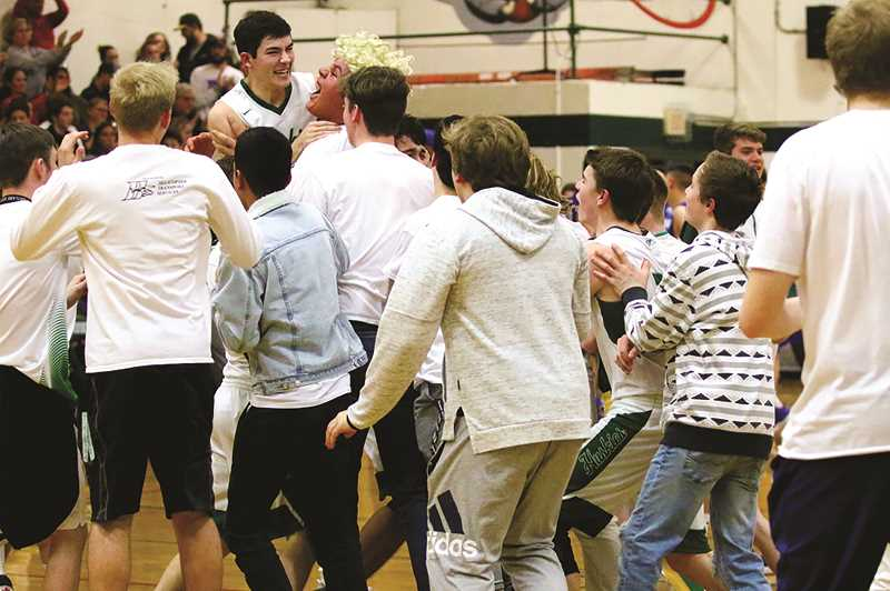 COURTESY: JO WHEAT - The North Marion boys basketball team celebrate with fans who stormed the court after the Huskies clinched their first round victory over Valley Catholic on Friday.