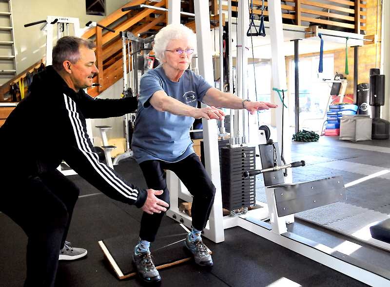 GARY ALLEN - Progressive Fitness owner David Allen aids Evelyn Piersall in proper technique while doing squats last week.