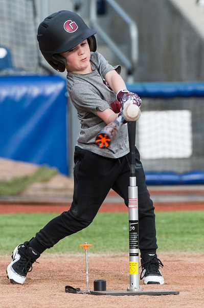 PMG PHOTO: CHRISTOPHER OERTELL - Elijah Culbertson, 7, from Hillsboro, hits a ball off a tee during the Pitch, Hit and Run competition at Ron Tonkin Field in Hillsboro, Ore., on March 10, 2018.