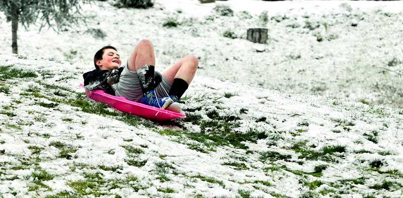 GARY ALLEN - A youngster braves the cold in shorts after a brief skif of snow descended on Newberg last week.
