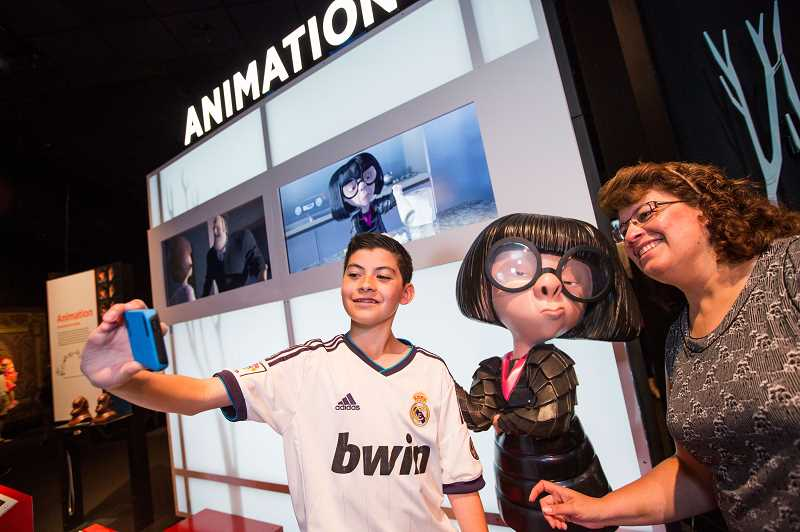 SUBMITTED PHOTOS:  - Visitors to OMSIs the Science Behind Pixar exhibit pose with models of some of their favorite Pixar characters including Edna Mode.