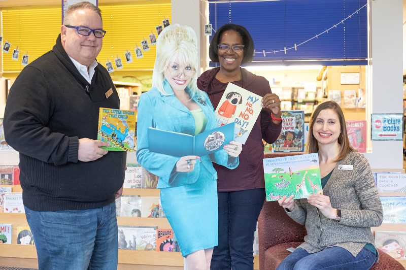 TIDINGS PHOTO: JONATHAN HOUSE - From left, Doug Erickson, Dolly Partons lifesize cardboard cutout, Martha Swanson, and Sarah Flathman with a few books offered through the Imagination Library program.