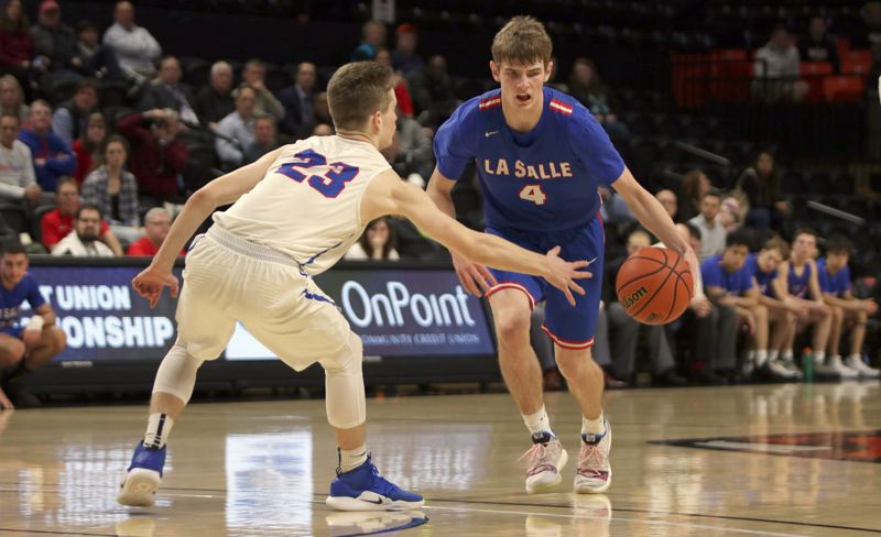 PMG PHOTO: JIM BESEDA - Churchill's Evan Pia (23) made it difficult for La Salle Prep's Jace Norton (4) to find room to maneuver, helping hold the Falcons' leading scorer to 13 points on 4-for-9 shooting Wednesday.