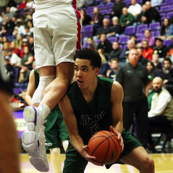 PMG PHOTO: DAN BROOD - Tigard High School sophomore Drew Carter ducks below a South Salem player before making a pass during Wednesday's game at the Class 6A state tournament.