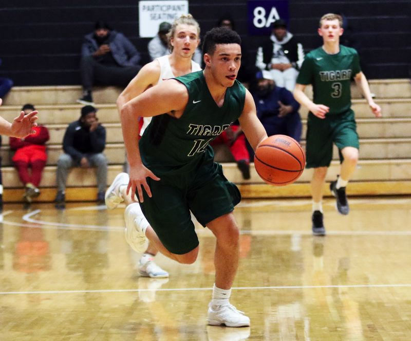 PMG PHOTO: DAN BROOD - Tigard High School junior Max Lenzy brings the ball up court on a fast break during Wednesday's game at the Class 6A state tournament.