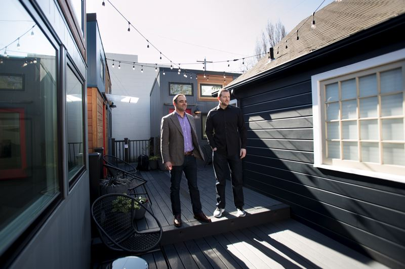 PMG PHOTO: JAIME VALDEZ - Slabtown Village owners Grant Norling, left, and John Jendritza show off a deck area that connects three tiny homes and the smallest of a trio of Victorian houses that make up the citys newest tiny house hotel.