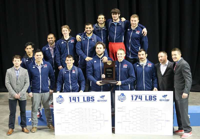 PHOTO COURTESY OF NJCAA  - The Clackamas Community College wrestling team stands with the awards they earned for winning the National Junior College Athletic Association championship. CCC head coach, Josh Rhoden, far right, is a Crook County High School graduate.