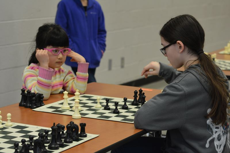 PMG PHOTO: COURTNEY VAUGHN - Alice Song watches as Lucy Dobson makes a move during a chess game held Saturday, March 2. The game was one of several rounds of the inaugural Mike Sheehan Memorial Chess Tournament in Scappoose.