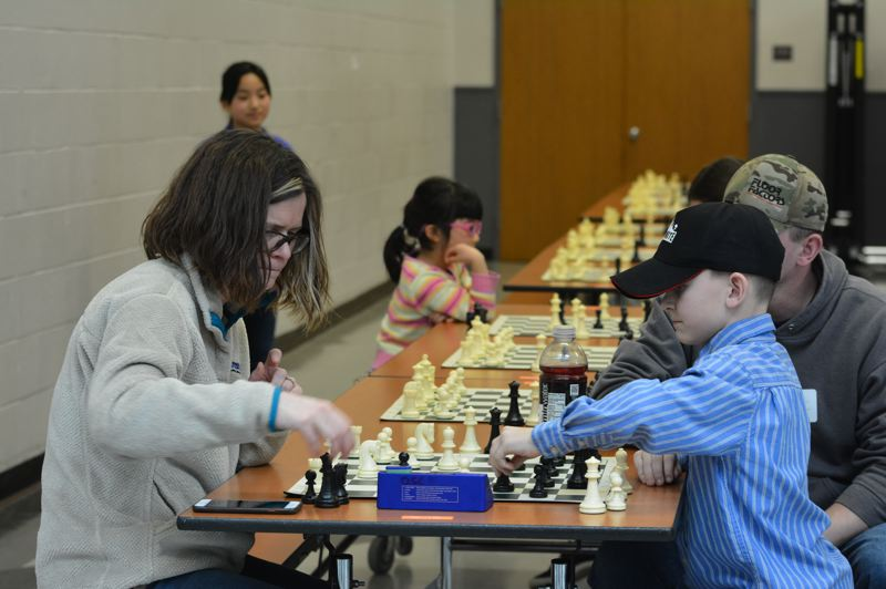 PMG PHOTO: COURTNEY VAUGHN - Alli Massey plays a friendly game of chess with Keagan DuBach, 8, during the Mike Sheehan Memorial Chess Tournament.