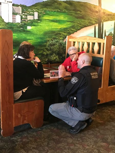 SUBMITTED PHOTO: SCAPPOOSE POLICE DEPARTMENT - Dennis Viereck of the Scappoose Police Department greets a table of customers at Ixtapa Family Mexican Restaurant during Tip-a-Cop night Saturday, March 2.