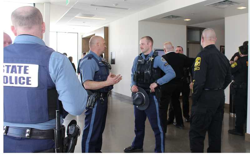HOLLY M. GILL/MADRAS PIONEER - Law enforcement officers and emergency responders who attended the sentencing of Christopher Sweeney, 20, on March 1, gather outside the courtroom. Sweeney was sentenced to 20 years in prison for two counts of aggravated attempted murder for attempting to fire a gun at an Oregon State Police officer and a Jefferson County Sheriff's Office deputy.