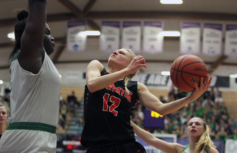 PMG PHOTO: MILES VANCE - Beaverton's Mary Kay Naro attacks the basket while defended by West Linn's Aaronette Vonleh during the Beavers' 50-42 win in the quarterfinals of the Class 6A state tournament at the Chiles Center on Thursday.