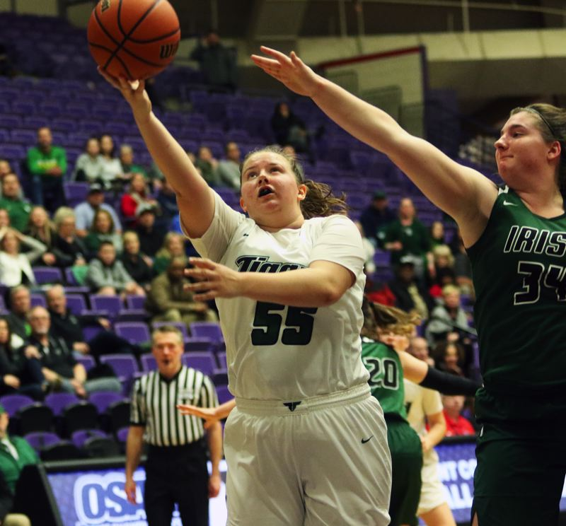 PMG PHOTO: DAN BROOD - Tigard High School senior Dani Lyons (left) goes to the basket for a layup during the Tigers' state tournament game with Sheldon.