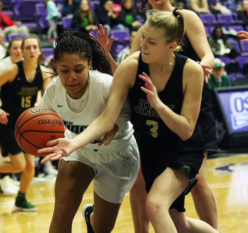 PMG PHOTO: DAN BROOD - Tigard sophomore Ajae Holdman (left) tries to keep the ball away from Jesuit senior Elsa Hookland during Friday's Class 6A state tournament game.