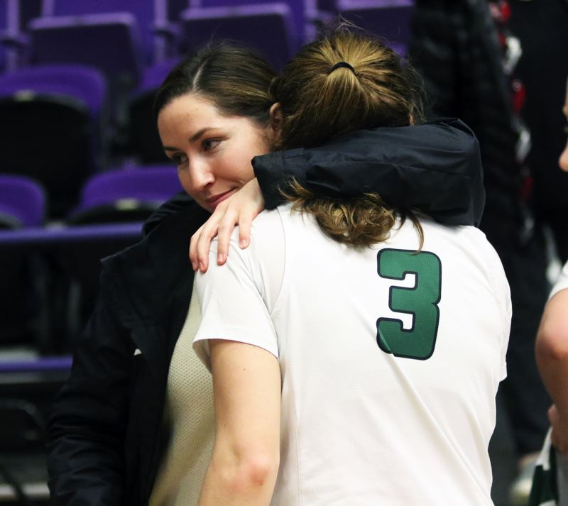 PMG PHOTO: DAN BROOD - Tigard senior Campbell Gray gets a hug from Tigard athletic trainer Sarah McSweeney following the Tigers' 45-43 state tournament win over Jesuit on Friday.