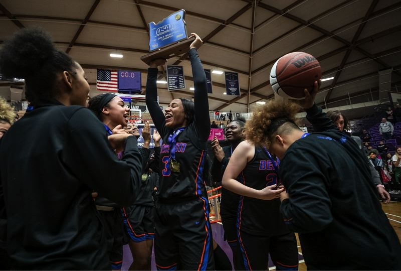PAMPLIN MEDIA GROUP: JONATHAN HOUSE - Ciera Ellington, surrounded by her Benson teammates, holds up the state championship trophy after the Techsters' 66-42 runaway victory Saturday night over Southridge at Chiles Center.