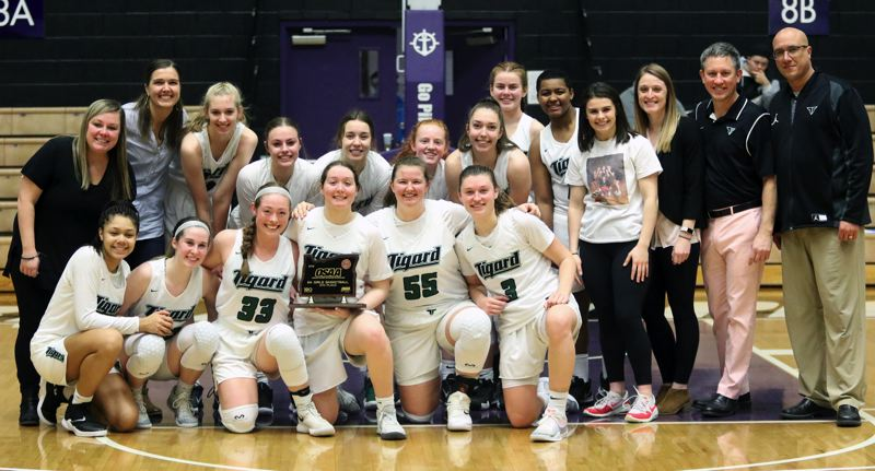 PMG PHOTO: DAN BROOD - Tigard High School girls basketball players and coaches gather with the fourth-place trophy following the Tigers' 44-34 win over West Linn Saturday at the Class 6A state tournament.