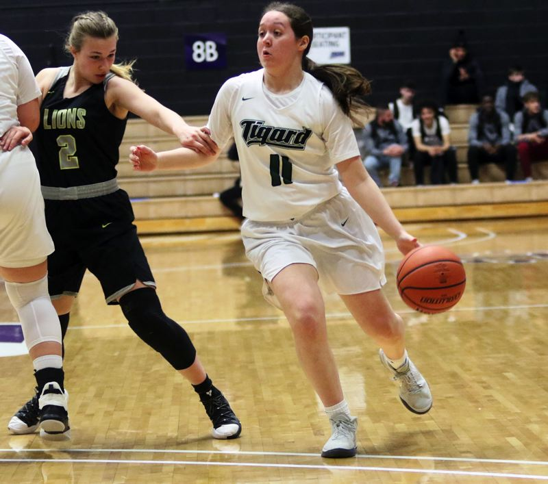PMG PHOTO: DAN BROOD - Tigard senior Paige LaFountain (right) drives past West Linn sophomore Cami Fulcher during Saturday's state tournament fourth-place game.