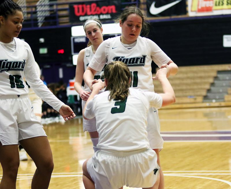 PMG PHOTO: DAN BROOD - Tigard senior Paige LaFountain (11) helps up senior Campbell Gray after she is fouled during Saturday's state tournament game.