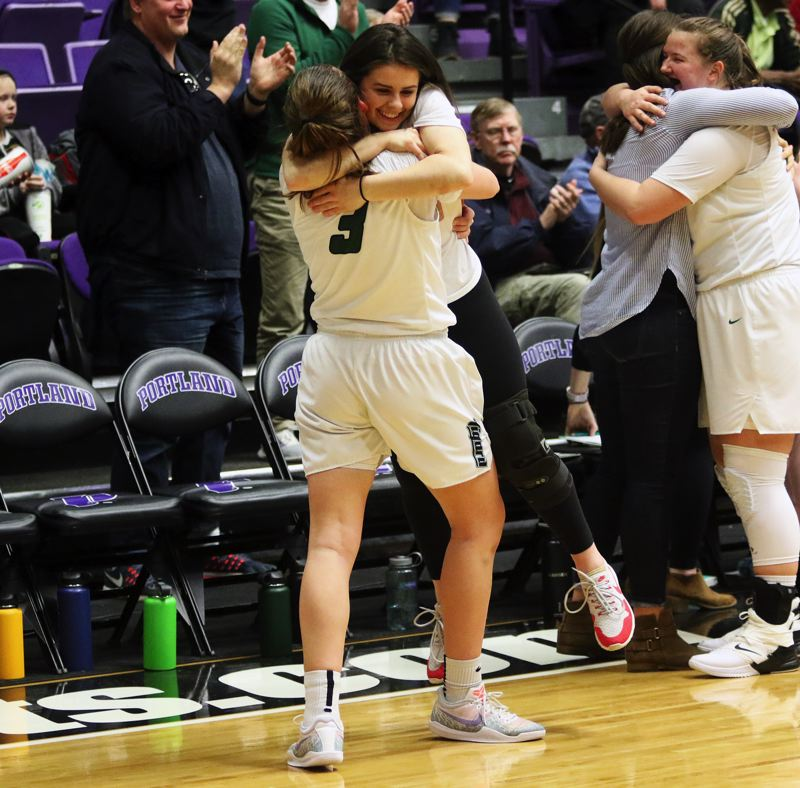 PMG PHOTO: DAN BROOD - Tigard High School senior Campbell Gray (3) hugs injured teammate Kennedy Brown during the Tigers' state tournament win over West Linn on Saturday.