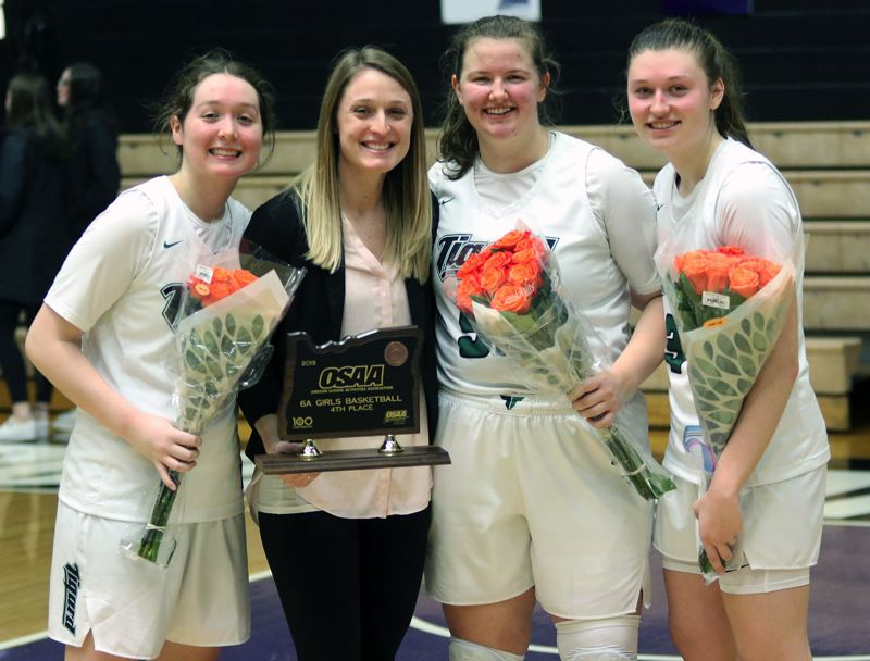 PMG PHOTO: DAN BROOD - Tigard seniors (from left) Paige LaFountain, Dani Lyons and Campbell Gray, here with Tiger assistant coach Mallory Goldammer following Saturday's state tournament win over West Linn, wrapped up their high school basketball careers.