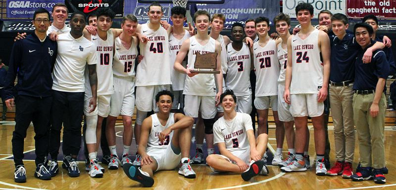 PMG PHOTO: MILES VANCE - The Lake Oswego boys basketball team is all smiles as it poses with its third-place tournament trophy after beating South Salem 80-63 on Saturday at the Chiles Center.