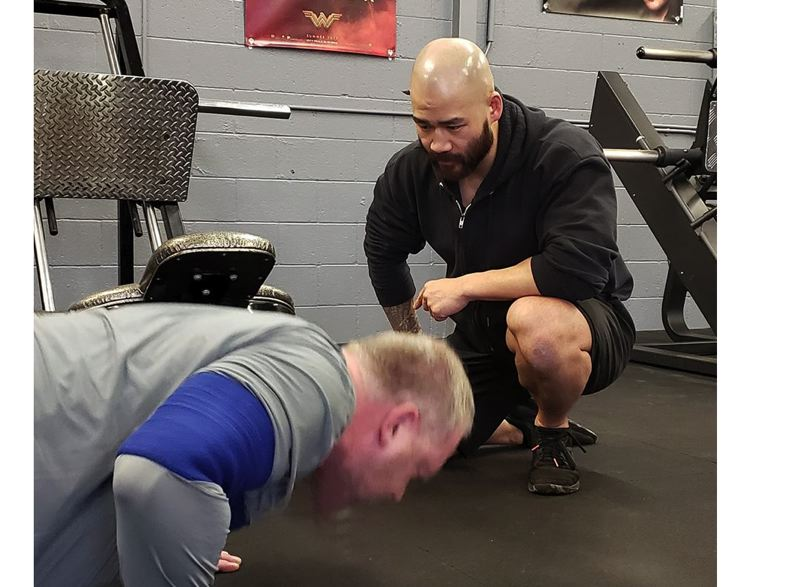 COURTESY PHOTO - Happy Valley resident Ryan Achenbach, owner of Valley Strength and Fitness, works with a client on push-ups.