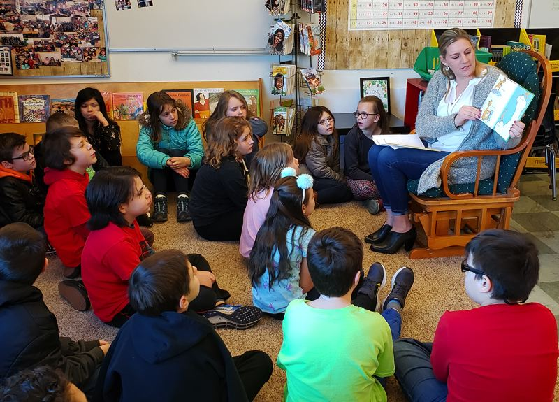 Parent volunteer Jennifer Fraga reads 'The Giving Tree' and some favorite Dr. Seuss books to fourth-graders in Ms. Brittany Vulgan's class at Holcomb Elementary School in Oregon City. The event was part of a nationwide celebration of reading.
