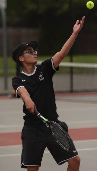 PMG PHOTO: DAVID BALL - David Douglas Kenton Bui tosses up a service ball during a match last season. He went 10-1 out of the Scots No. 1 doubles spot.