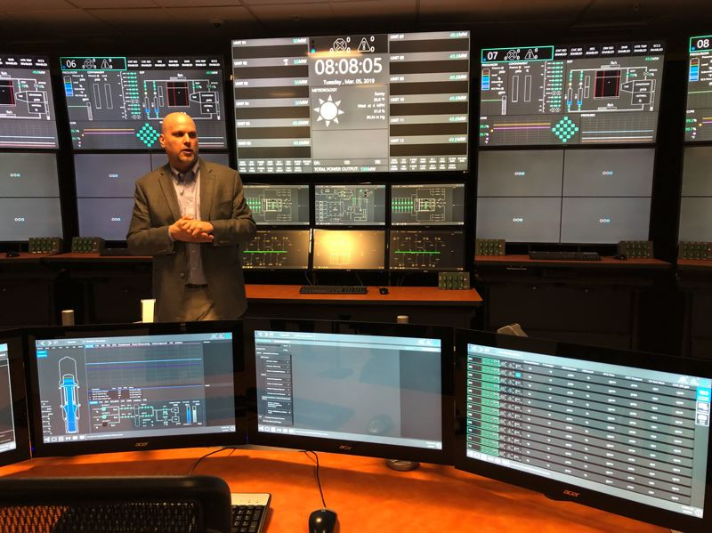 PAMPLIN MEDIA GROUP: STEPHANIE BASALYGA - Ross Snuggerud, a NuScale plant operations supervisor, shows off a full-size simulation of an operators room. The room, built at the company's Corvallis location, is similar to the one that will be used at the nuclear power plant planned in Idaho.