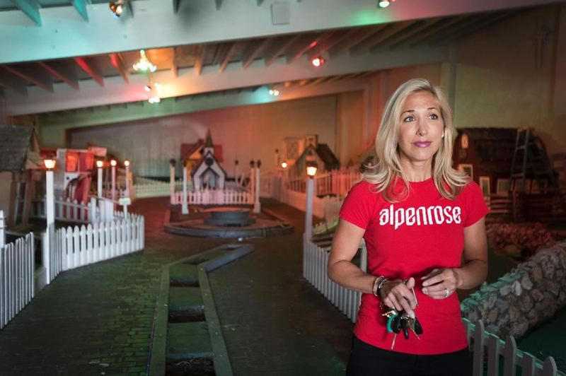 PMG PHOTO - Tracey Cadonau McKinnon, a third-generation member of the family that started Alpenrose Dairy, stands inside Storybook Lane at Dairyville where the room is filled with Christmas-themed houses.