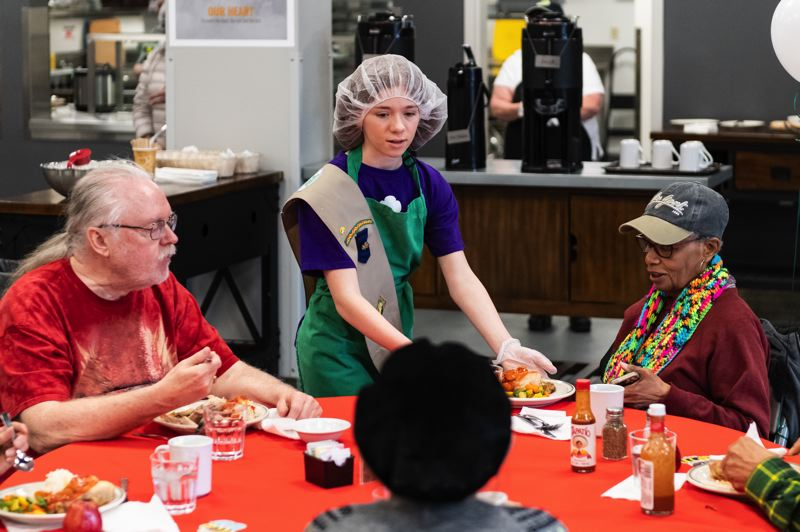 PMG PHOTO: CHRISTOPHER OERTELL - Girl Scout Jaylin Hogan, 12, from troop 40478 serves a meal to a guest eating lunch with the Meals on Wheels People in Hillsboro.
