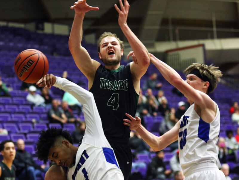 PMG PHOTO: DAN BROOD - Tigard High School senior Stevie Schlabach (4) has the ball knocked away by Grant's Aaron Deloney (left) and Max von Arx during the state tournament fourth-place semifinal game.