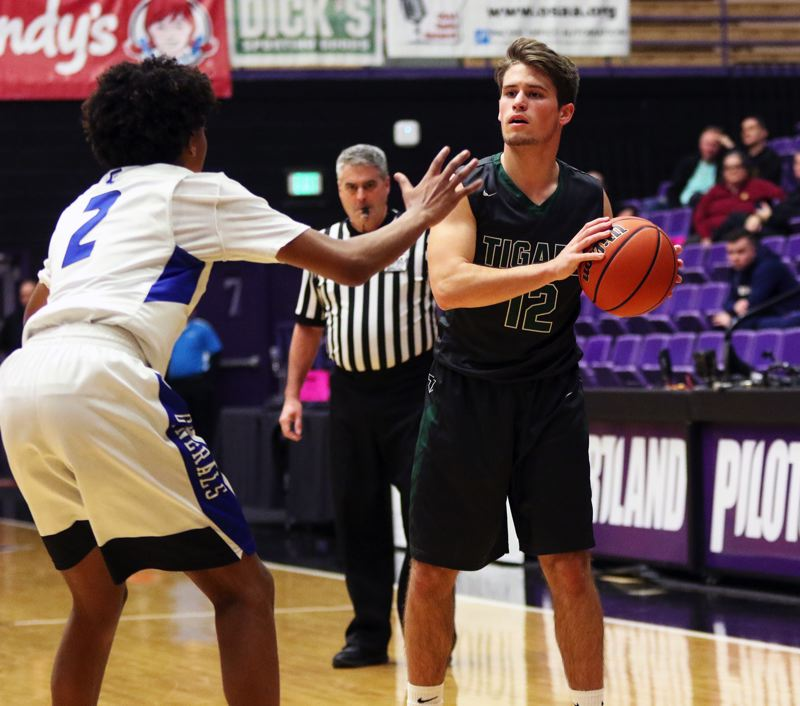 PMG PHOTO: DAN BROOD - Tigard High School senior guard Carson Crist (right) looks to pass the ball inside during the Tigers' state tournament game with Grant.