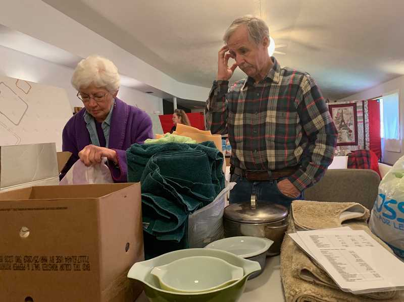 PMG PHOTO: GEOFF PURSINGER - Love INC volunteers Curtis Akesson and Doris Wilson sort through donations at the nonprofits new donation ceter at City Gate Church in Hillsboro. The donations will go to needy families across the city.