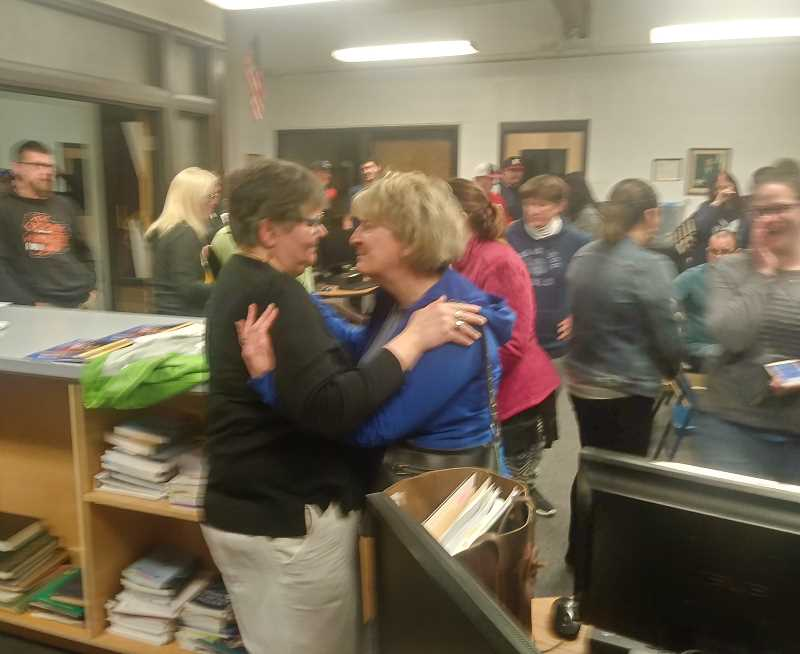 PMG PHOTO: JUSTIN MUCH - Well wishers embrace Mount Angel Middle School sixth-grade teacher Stacy Boost as the school board overturned a recommendation to not renew her contract.