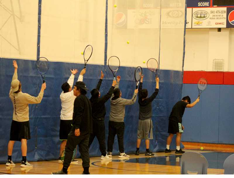 STEELE HAUGEN - The boys tennis team practices their serves while being inside the gym due to weather.